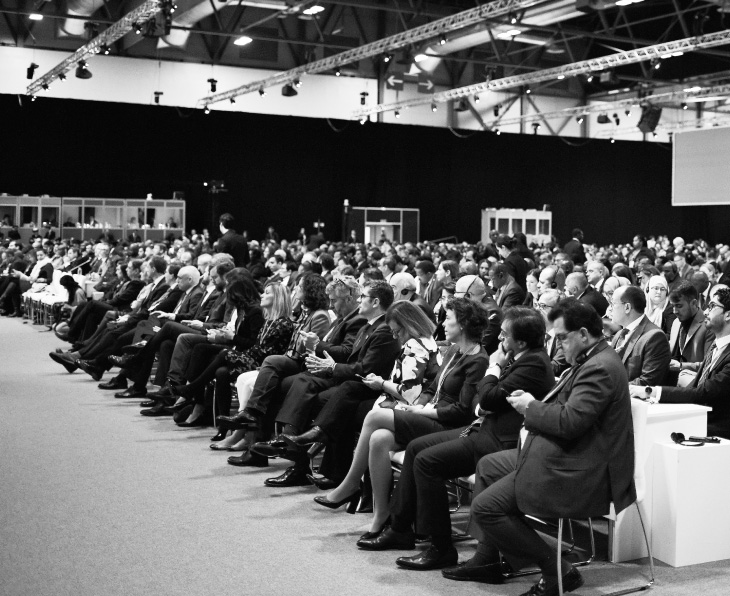 A black and white image of an audience sitting at a conference