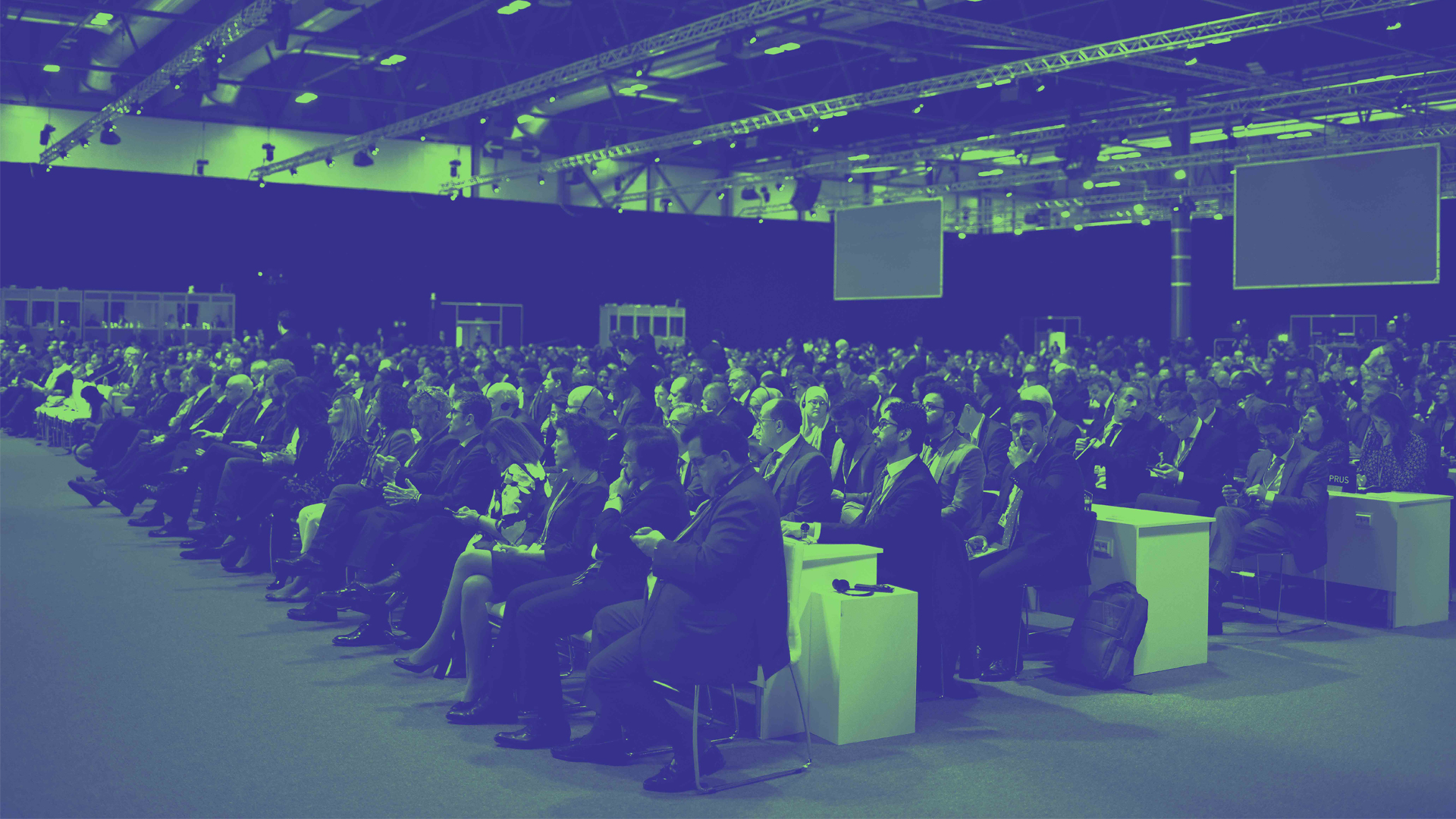 A photograph of an audience sitting at a conference, colourised in green and blue