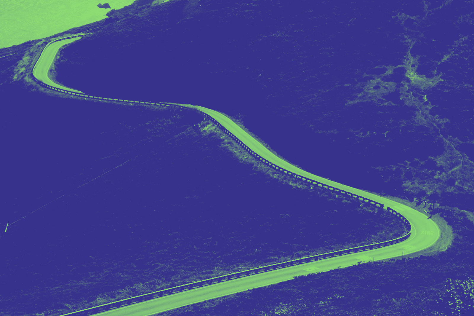 A photograph of a winding road cutting across hills, colourised in green and blue