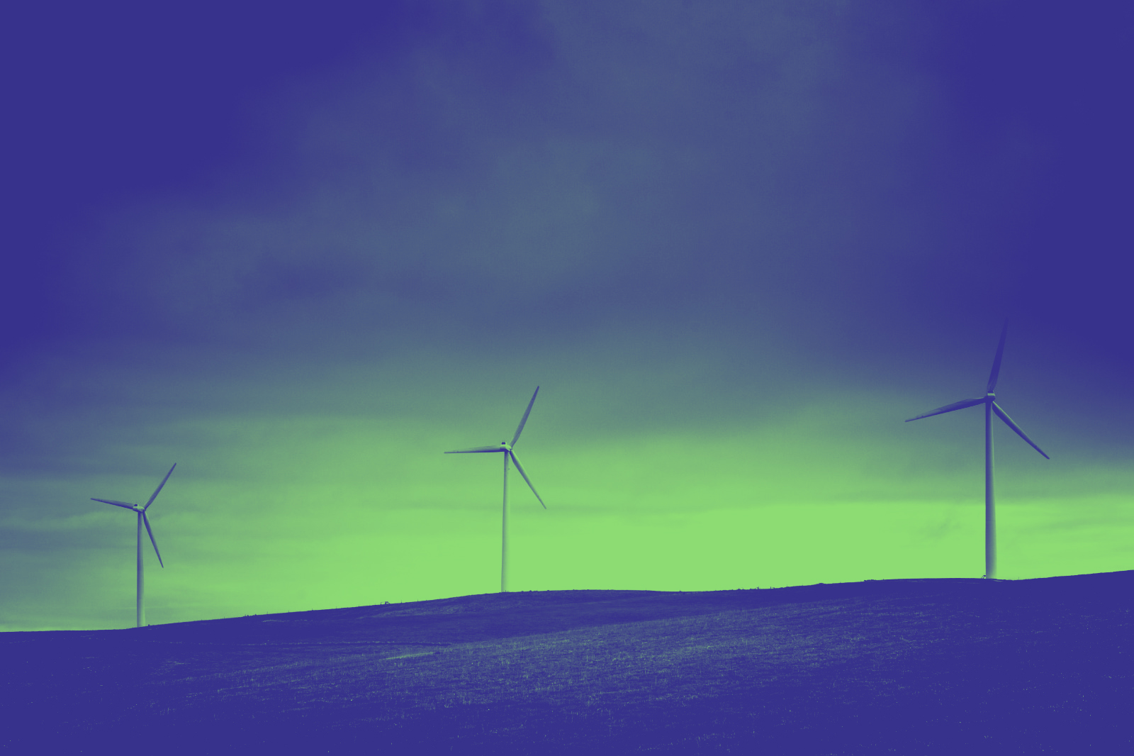 A photograph showing three wind turbines on a hill, colourised in green and blue